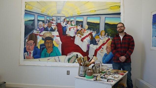 L'artiste Evin Collis pose devant un de ces tableaux où l'on voit les gens qui voyagent assis dans un train.
