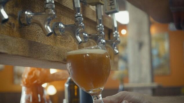 Une coupe se remplie de bière en fût dans une microbrasserie