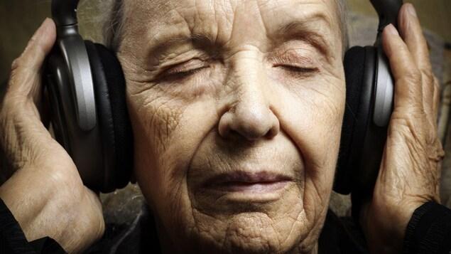 Une femme âgée écoute de la musique dans des écouteurs et son visage évoque le bien-être.