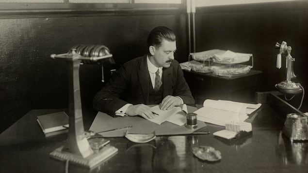 Photo en noir et blanc montrant un homme assis derrière un bureau en train de lire des documents.