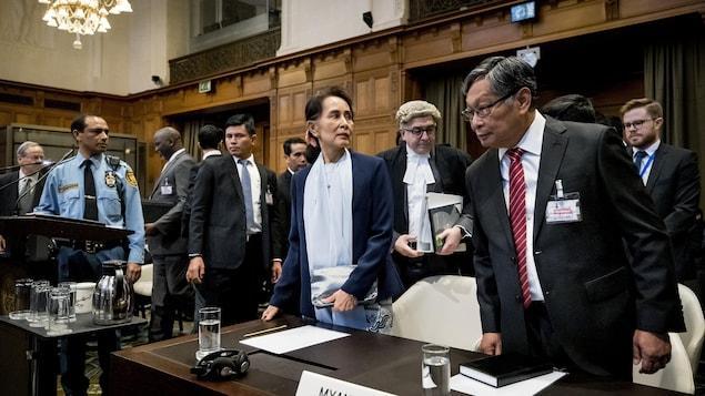 Aung San Suu Kyi est debout dans la salle d'audience, entourée d'autres responsables birmans.