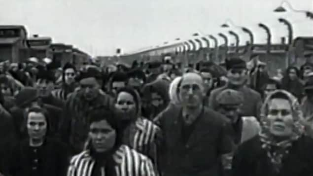 Image d'époque en noir et blanc de prisonniers dans un camp de concentration non identifié.