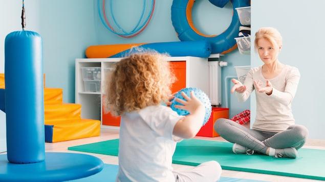 Un enfant autiste et sa thérapeute, jouant au ballon.