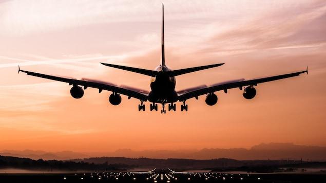 Un avion en train d'atterrir au coucher du soleil.
