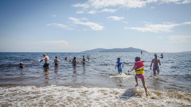 Plusieurs Septiliens se baignent aux plages de Sept-Îles, sous un radieux soleil.