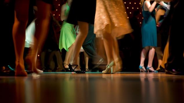 Des femmes avec des chaussures à talon et des robes dans un bal de finissants.