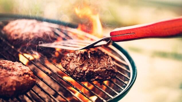 Trois steaks de viande cuisent sur un barbecue au charbon de bois.