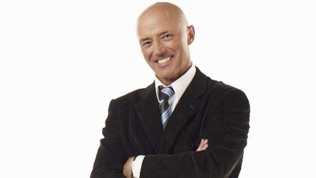 Un homme en costume et souriant pose de face, les bras croisés.