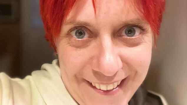 Un dame prend un égo-portrait. Elle est souriante et a les cheveux teints en rouge.