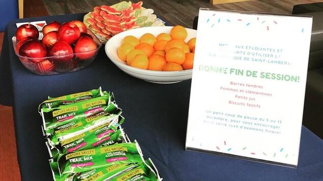 Une table sur laquelle se trouvent des pommes, des clémentines, des barres tendres et des biscuits de Noël.