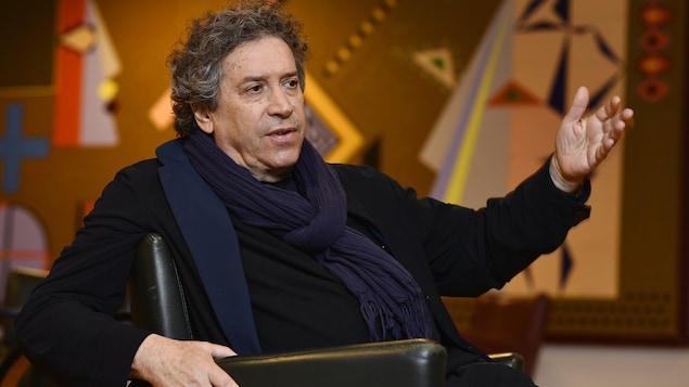 Franco Dragone, assis dans un fauteuil, parle en levant le bras.