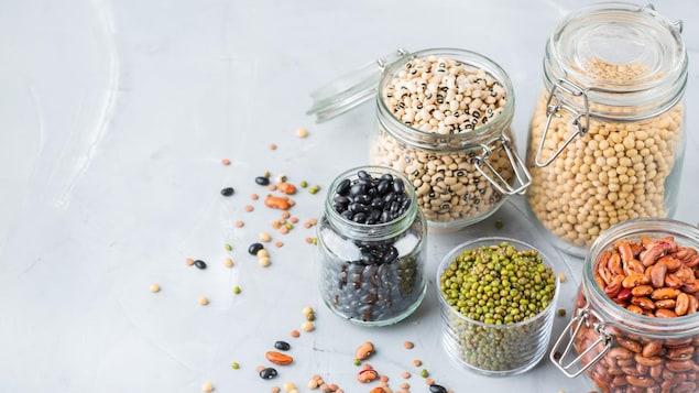 Des haricots noirs, blancs et rouges, des lentilles et des pois chiches dans des bocaux.