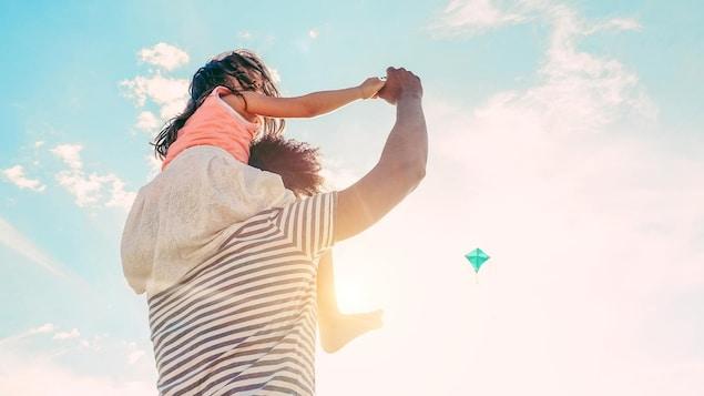 Un homme tient une petite fille sur ses épaules.