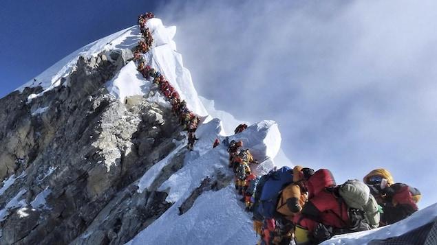 De nombreux alpinistes font la file avant d'atteindre le sommet de l'Everest.