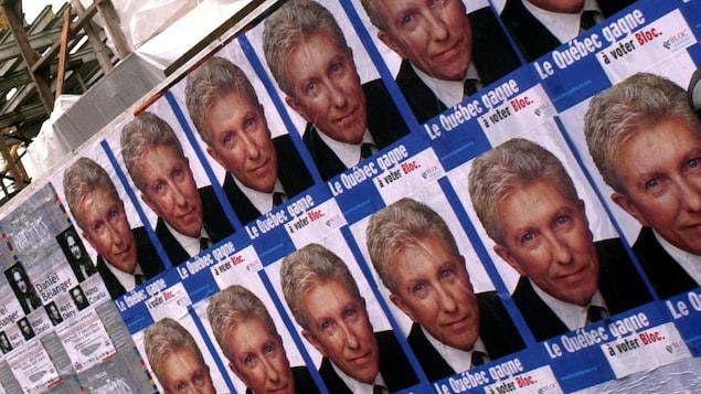Affiches électorales du Bloc québécois montrant le chef Gilles Duceppe, placardées en série sur un mur en 2000.