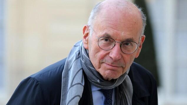 Un homme avec des lunettes et portant un foulard regarde la caméra.