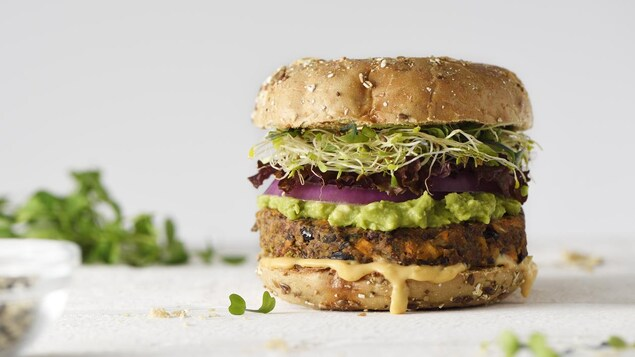 Gros plan d'un burger composé d'une boulette végétale, de guacamole, d'oignon et de graines germées.