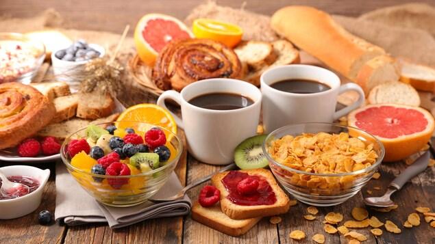 Table remplie de fruits, de café, de céréales, de pain et de viennoiseries.