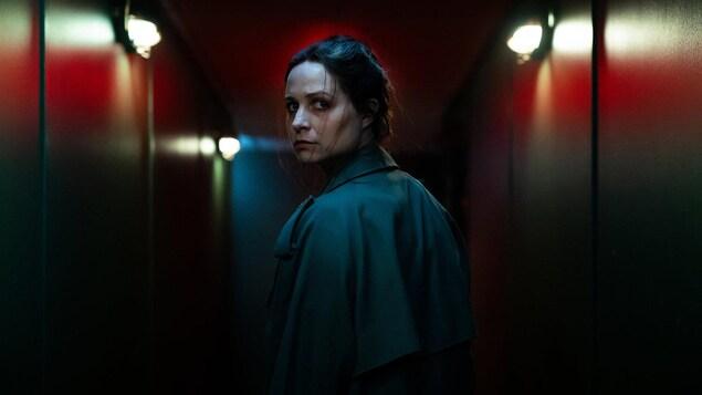 L'actrice jette un regard de dos, dans un couloir sombre.