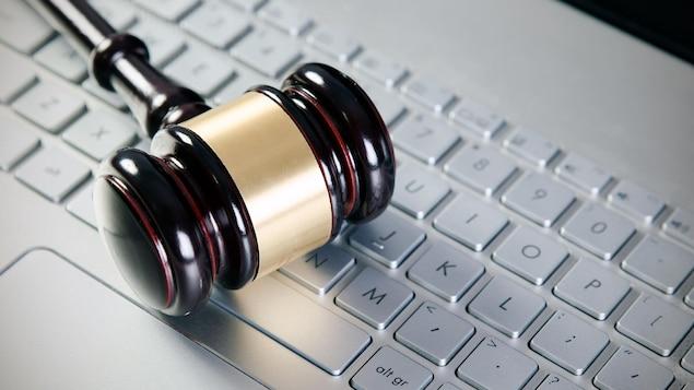 Un maillet de juge sur un clavier d'ordinateur.