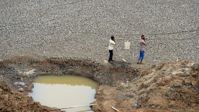 Deux travailleurs indiens transportent un seau d'eau puisée à même un étang asséché.