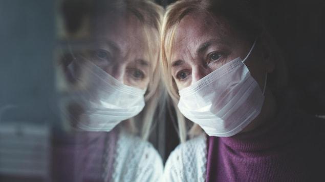 Une femme portant un masque a la tête appuyé sur une vitre.