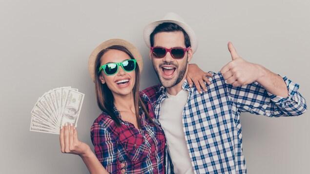 Une jeune femme et un jeune homme affublés de verres fumés montrent fièrement une liasse de billets de banque.