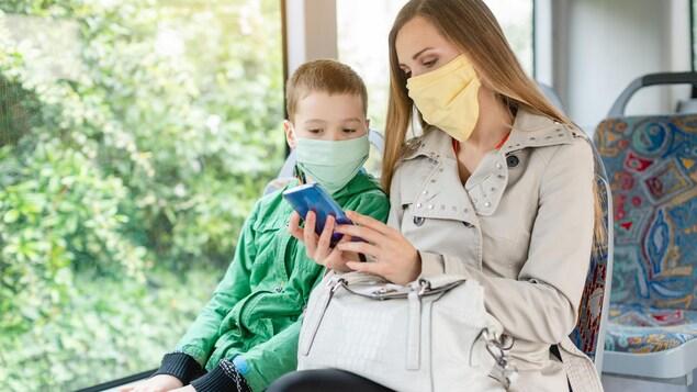 Une mère et son fils, vêtus de couvre-visages, consultent un téléphone intelligent.