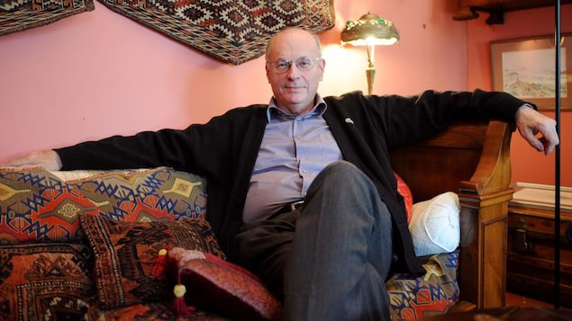 L'homme chauve est assis dans un salon, les bras étendus de chaque côté du sofa.