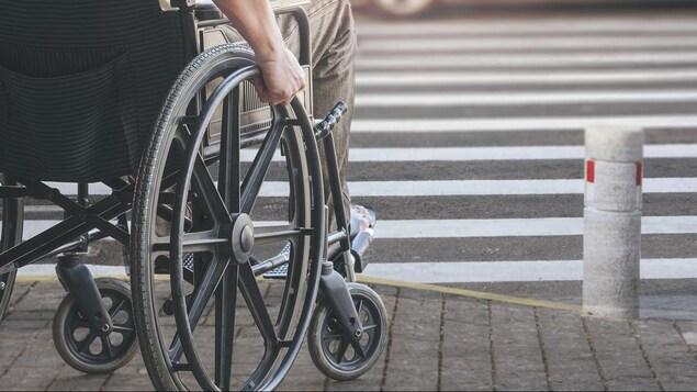 Un homme s'apprête à traverser la rue en fauteuil roulant.