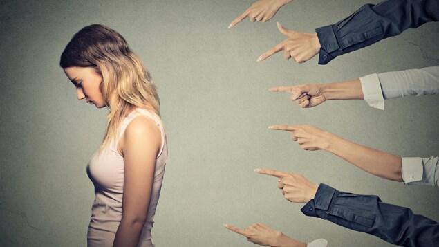 Une femme de profil est pointée du doigt par plusieurs personnes.