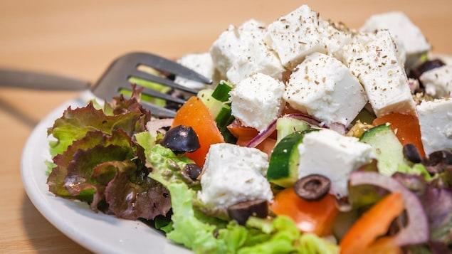 Une salade composée de feta, concombres, tomates, olives noires, oignons et laitue servie dans une assiette.