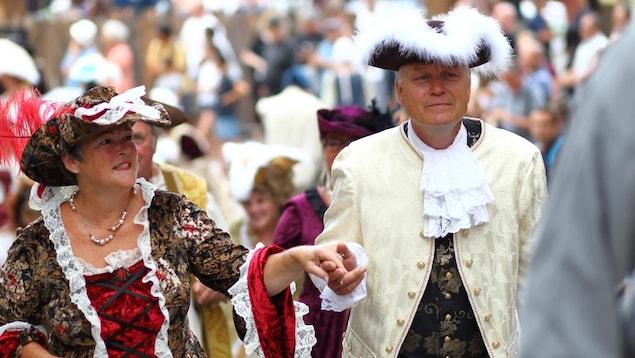 Un homme et une femme participent au défilé des Fêtes de la Nouvelle-France 2018.