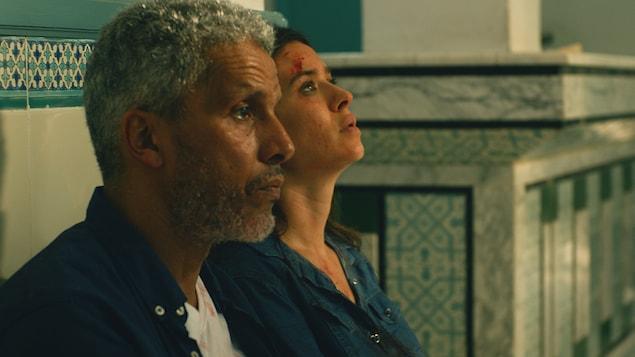 Un homme et une femme dont le visage est maculé de sang sont adossés contre un mur.