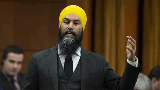 Jagmeet Singh, debout, lève le bras en s'adressant aux autres députés.