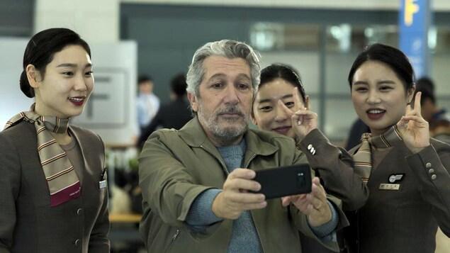 Un homme d'âge mûr prend une photo de lui avec des agentes de bord coréennes.