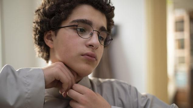 Un jeune garçon à l'air mélancolique attache son col de chemise.