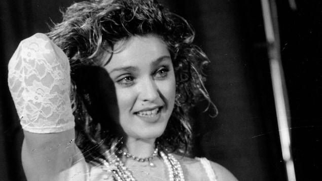 La chanteuse pose le bras droit levé en souriant aux photographe. Elle porte des chapelets, une robe de mariée et une ceinture avec une boucle Boy Toy.