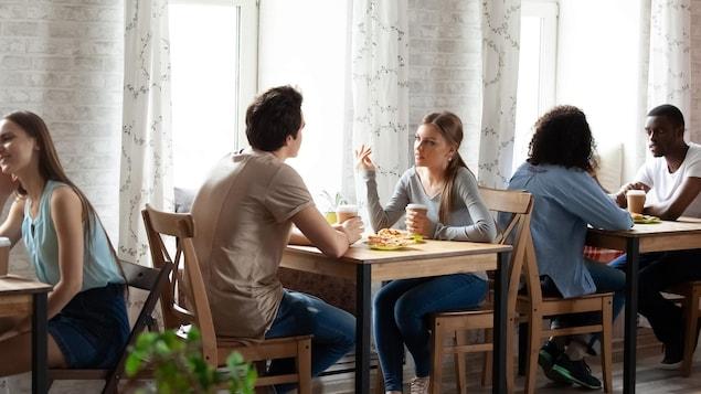 Des jeunes gens attablés à un restaurant discutent.