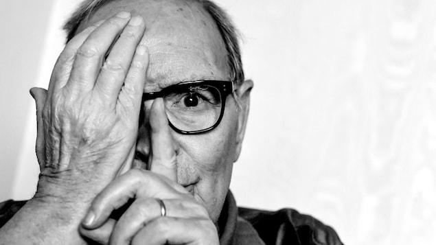 Le compositeur italien Ennio Morricone regarde la caméra avec une main cachant son œil droit.