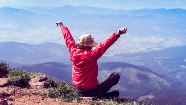 Une femme ouvre les bras devant un paysage montagneux.