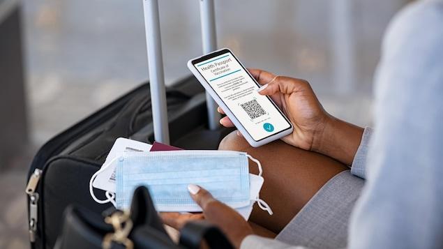 Une femme assise dans un aéroport vérifie son passeport de vaccination de la COVID-19 sur son téléphone, tout en tenant un masque et une carte d'embarquement.