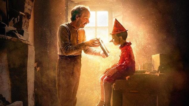 Roberto Benigni incarne Geppetto qui montre un objet à sa création de bois Pinocchio.