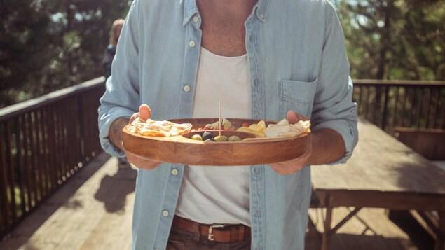 Un homme tient un plateau entre ses mains.