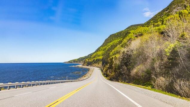 Une route entre fleuve et montagne, sans voiture.