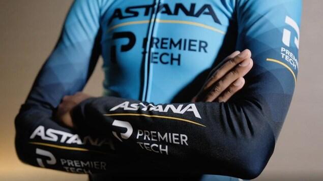 Un cycliste arbore le maillot avec le nom de l'équipe.