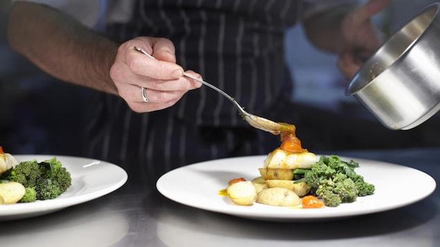 Un cuisinier dispose des légumes dans une assiette.