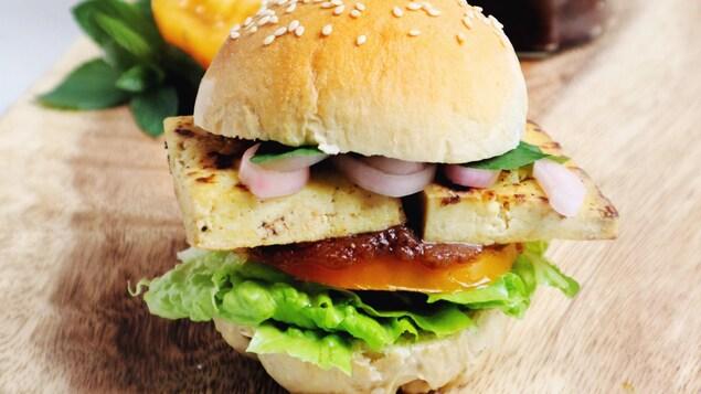 Un sandwich au tofu grillé et aux légumes sur une planche de bois.