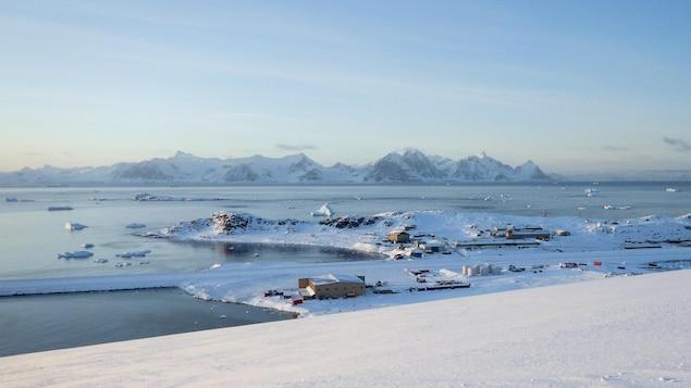 Paysage de mer, de montagnes et de côte enneigées où se trouve une station de recherche composée de plusieurs bâtiments.