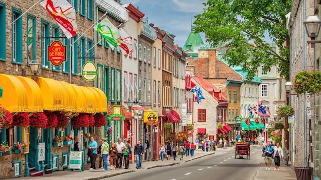 Des gens se promènent dans une rue colorée de la vieille ville.